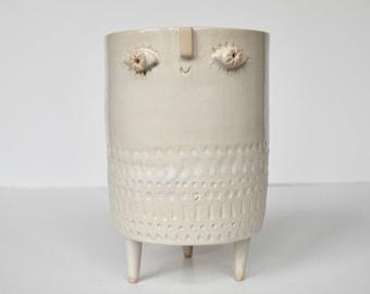 Large tripod pot with big eyes in white glaze