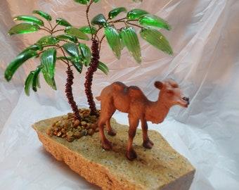 Camel figurine under the palm tree.