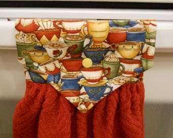 COFFEE cups adorn the top of the red hanging kitchen towel.