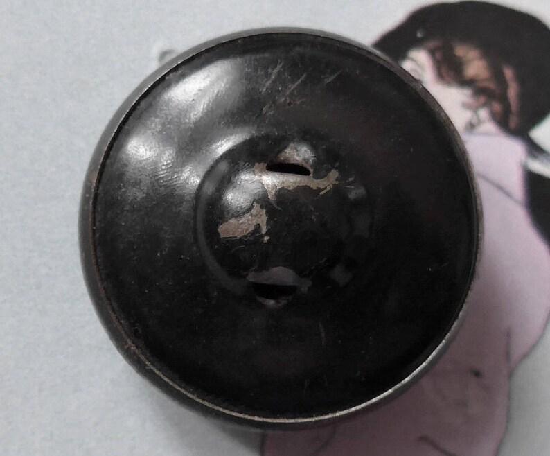 c1920. self shank vintage a decorative pressed black celluloid bubble set in a painted black metal rim Celluloid button