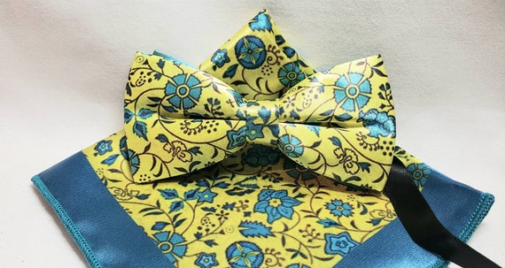 Polyester Teal and Yellow Flower Print with coordinating Pocket Square. Adjustable up to 20 inches with plastic bow tie slides.