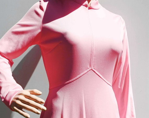 Long pink dress with sleeves and high collar, mod 70s fashion style.