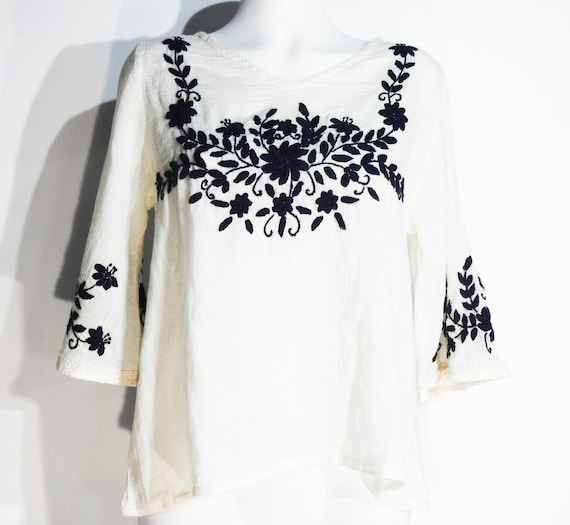 White top with blue embroidery