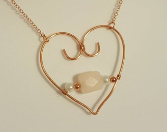 A delicate copper wire and pink opal heart shaped pendant on solid copper chain