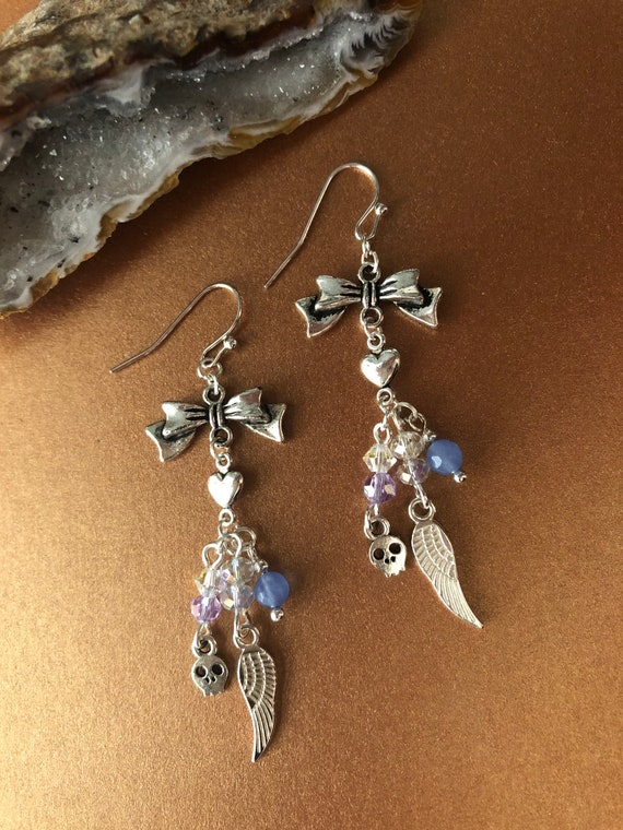 Twinkling Silver Wings skull heart bow earrings with blue stones