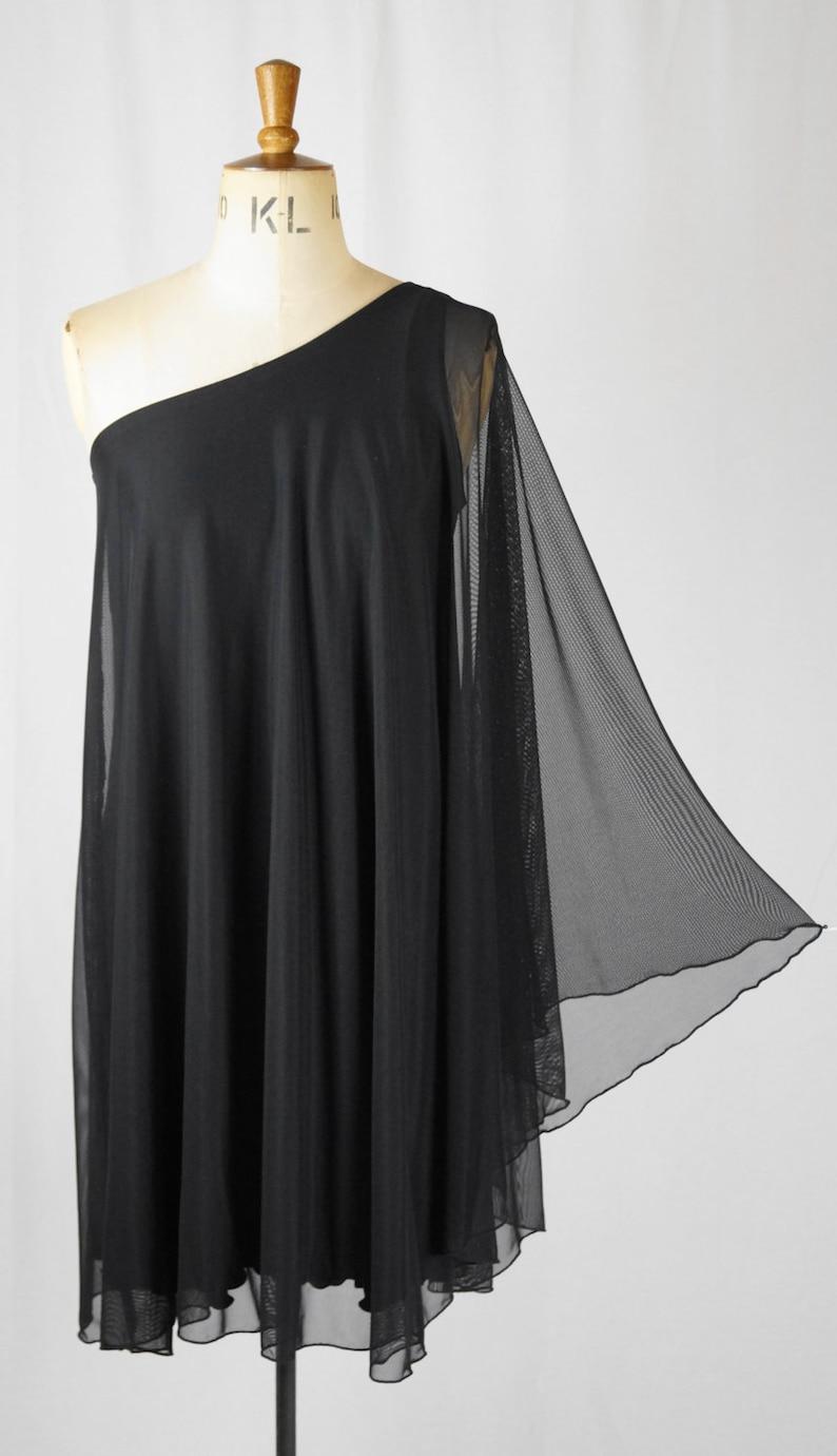 70s Jackets, Furs, Vests, Ponchos     Baylis & Knight SHEER STUDIO 54 Batwing 70s Disco Glam One Shoulder Bat Wing KNEE Dress Black Elegant (Smock) $84.54 AT vintagedancer.com