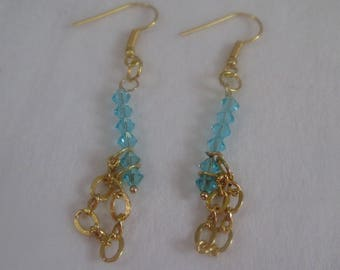 Earrings with turquoise swarovski. They have a gold plated chain that dangles  at the bottom.