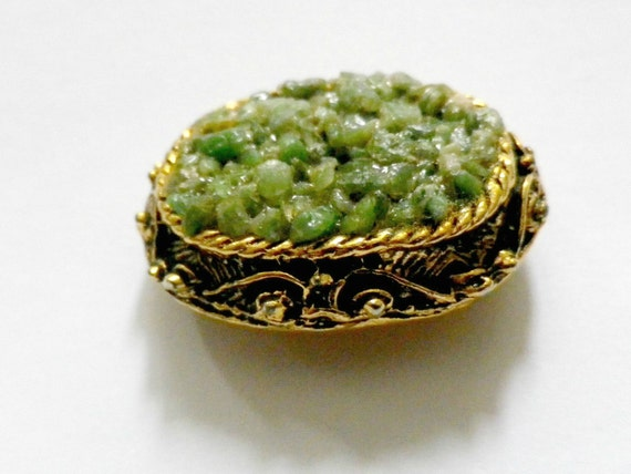 Art Nouveau style small oval brooch with green jade chips