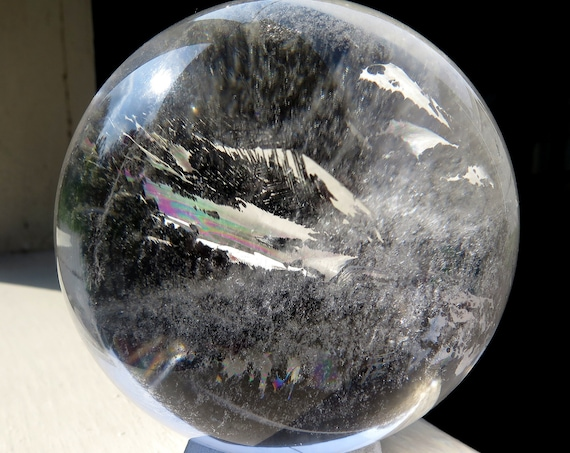 Large 3 7/8 inch across. Crystal rock Quartz Crystal ball. The sphere has some rainbows with a perfect surface. No damage. Internal foils.