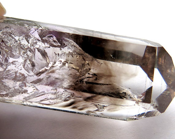 A 64.6 gram Enhydro Smoky Phantom crystal quartz with bubbles throughout. I count 4 and I'm sure there are more.