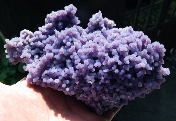 A high quality glistening Grape Amethyst. Indonesia. 6.25 inch across. Complete all around floater. 1 pound 9.9 ounce. No damage