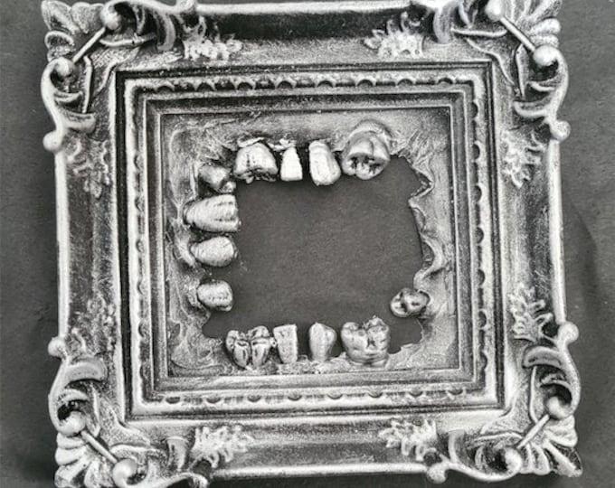Oddities - Silver Teeth Frame - Slight Damage