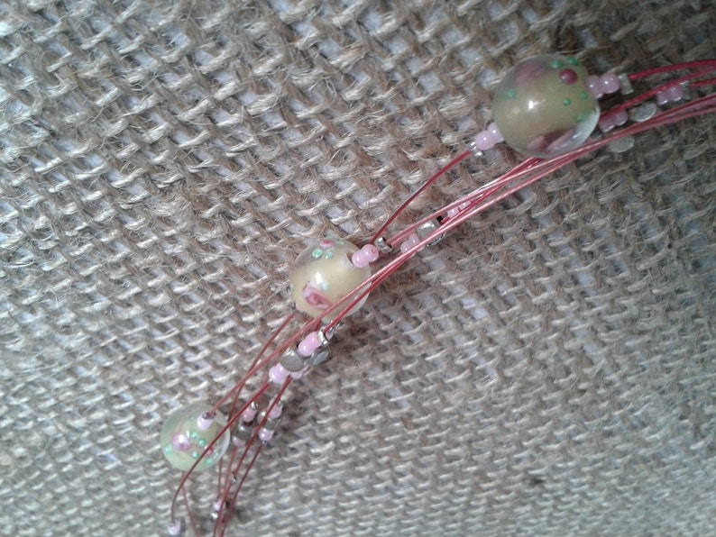 Airy light boho necklace with six pink coloured strings with glass and metal beads