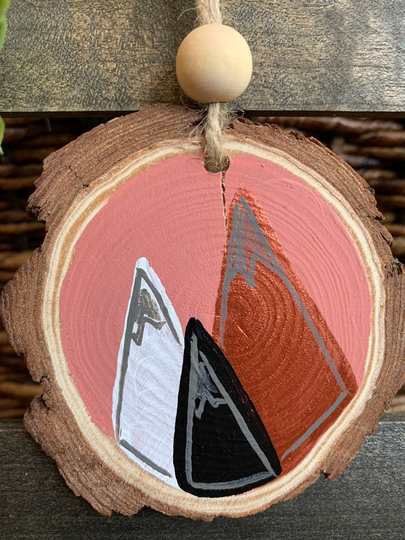 painted wood round ornament rosy metallic mountains