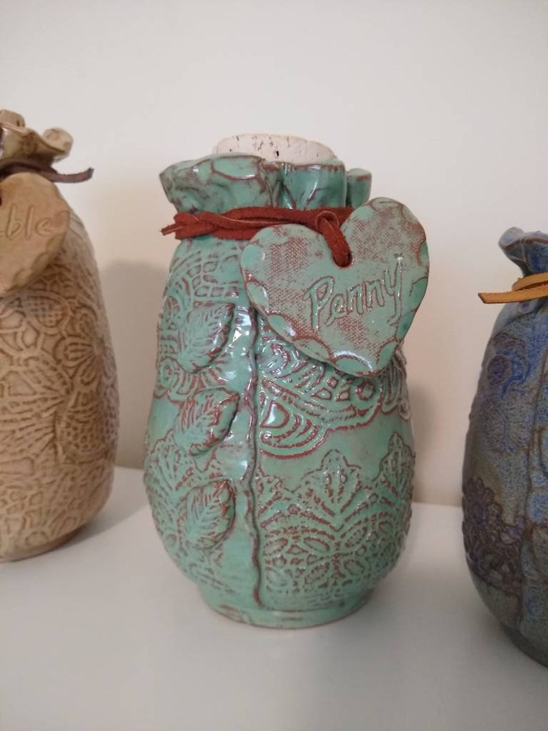 your choice of color and size. Ceramic Pet Urn is embossed with lace and personalized with a heart hung on a leather cord with pet/'s name