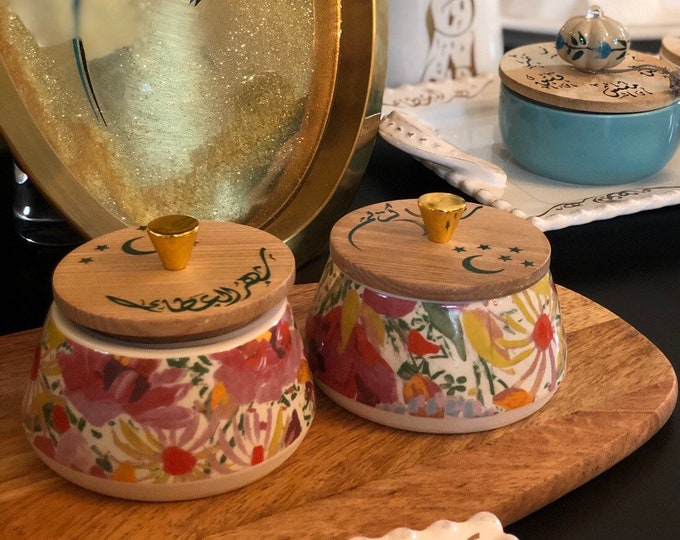 A set of two snack bowls with decorated wooden lids