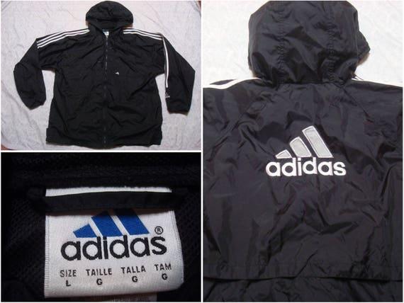 Vintage Herren 90 Adidas Jacke schwarz weißes großes Logo auf Rückseite drei Streifen Kapuze voll Reißverschluss Windjacke Spellout überdimensioniert