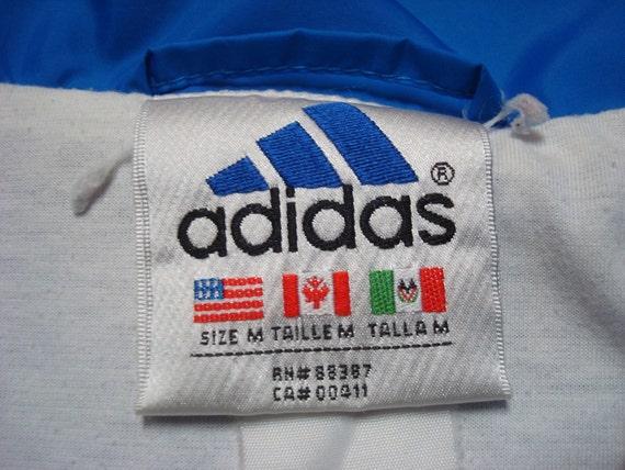Schwarze Adidas Jacke mit roten accessoires und weissen streifen & adidas zeichen