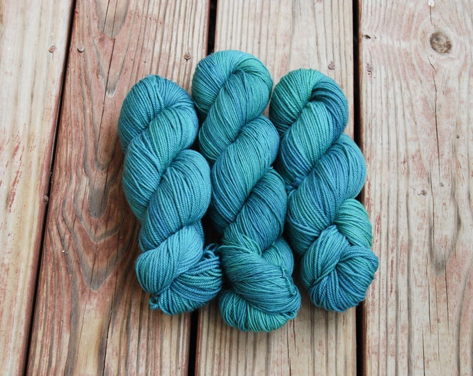 Featured listing image: Evergreen - Hand dyed semi-solid tonal yarn in medium and dark green with subtle blue undertones