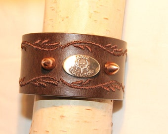 Brown mixed media cuff with 'Bone Collector' concho and brass bullet conchos