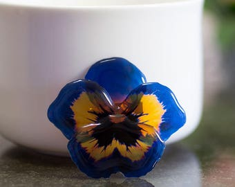Dark blue pansy brooch, handmade in Britain with resin, transparent and light. Comes in a gift box.