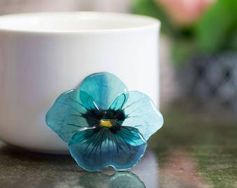 Teal pansy brooch, made by hand in UK with resin, transparent. Comes in a gift box.