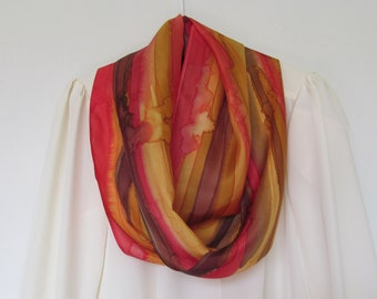 This is a hand painted, approximately 11 x 76 inch, 100% silk, infinity/circular scarf in gold, yellow brown and orange.