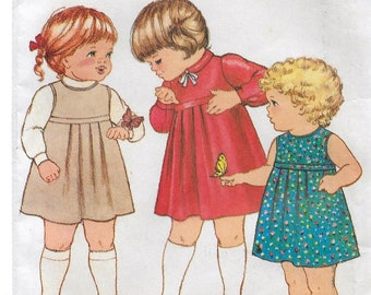 """A Flared A-Line, Back Button, Raised Waist Long Sleeve Dress or Sleeveless Jumper Pattern for Toddlers: Size 1, Breast 20"""" • Butterick 3999"""