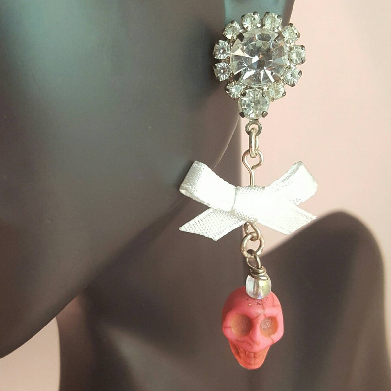 Rhinestone earrings featuring a white bow and pink skull image 0