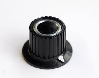 black skirted radio knob with white pointer and chrome ring