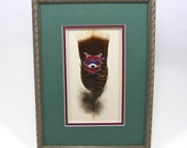 Purple Raccoon Bandit Hand Painted on Mississippi Wild Turkey Feather. Framed in Shadowbox. Matted with Moss Green and Purple.