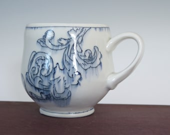 Handmade blue and white porcelain mug with scroll design