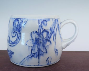 Handmade blue and white porcelain mug with floral toile pattern