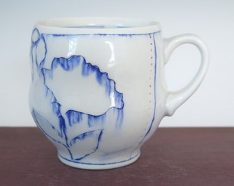 Handmade blue and white mug with blue floral pattern and red accent dots