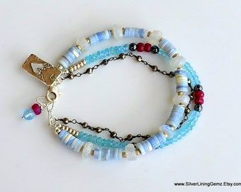 "Shades of Blue. Neon Apatite, Ruby, Hematite, Rainbow Moonstone and Blue Silverite Three Strand Bracelet. SA 7-7.5"". Cut out Heart Tag."
