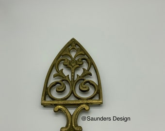 A vintage Ornate Brass Flat Iron Trivet