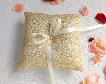 Ivory wedding ring pillow decorated with gold glitter net. Gold ring bearer.