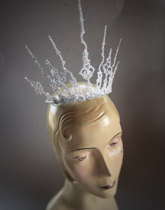 Winter wonderland Ice Queen style over the top crown for your awesome event. Securely attaches with a skinny elastic strap tucked under the hair at the back of the neck.