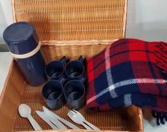 Vintage Aladdin wicker family picnic basket set with plates, silverware, cups, thermos, and blanket