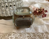 Antique thickly beveled glass and ornate metal jewelry casket
