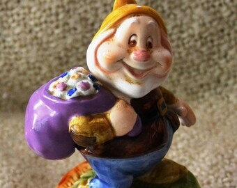 """HAPPY, ( one of the Seven Dwarfs.) Ceramic, with Sack on Shoulder,Schmidt,  80s, for WALT DISNEY Prod. Rotates & plays """" Make Someone Happy"""""""