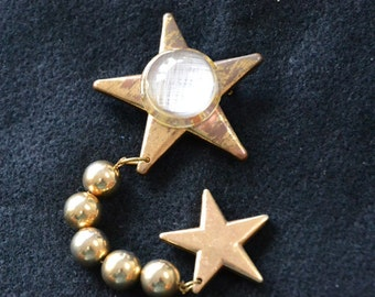 Brooch with 2 Gold Leaf Stars, Smaller Star hangs freely from Larger Star by 5 Goldtone Balls. Large Star has center of (Crystal-like Ball.)