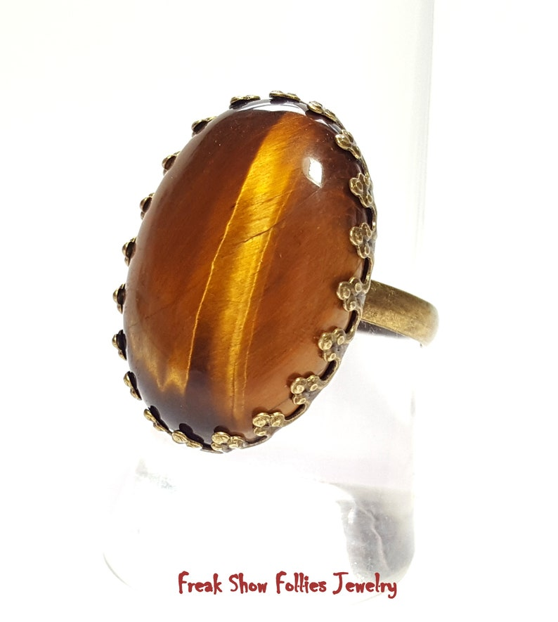 oval golden tigers eye gemstone ring in a bronze crowned prong setting
