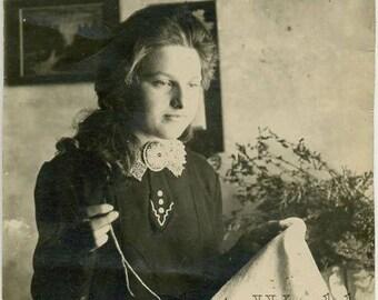 Pretty woman embroidering antique photo