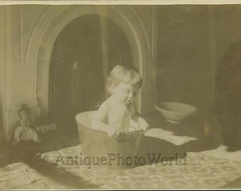 Cute child taking a bath in bucket antique photo