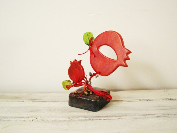 Ceramic pomegranates sculpture, set of two pomegranates on brown, square base, large and small pomegrantes with green leaves and red ribbons