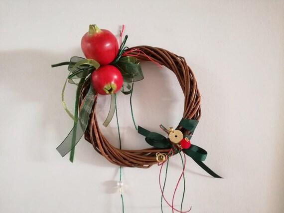 Ceramic pomegranates wreath, wicker and pomegranates wreath of red pomegranates and green ribbons, wicker, ribbons and strings, Xmas wreath