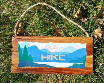 Painted Wood Sign with Landscape and Take a Hike Lettering in Gold