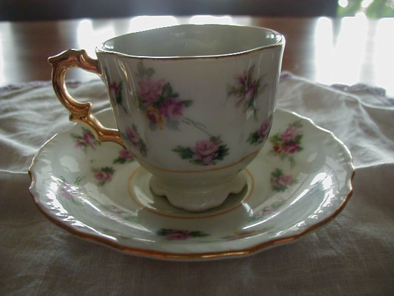 Very nice Made in Occupied Japan cup and saucer with lovely pink flowers  and gold trim  Measures saucer 4 3/4 cup 2 1/2 in  tall