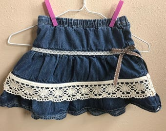 Girls, 24 Months denim skirt with embroidery trim and bow.